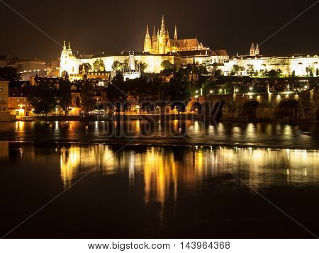 Night Prague Castle with St Vitus Cathedral and Charles Bridge reflected in Vltava river, Prague, Czech Republic