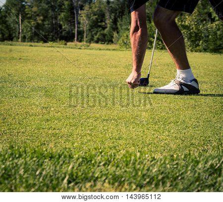 Golfer pushing in tee in prince edward island