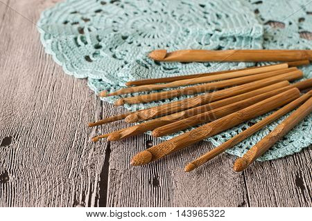 A set of wooden hooks and knitted napkin on a gray wooden table. Selective focus.