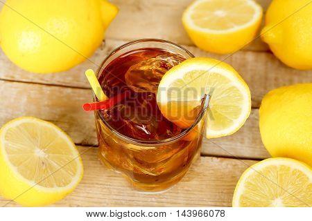 glass of ice tea with lemons on wood