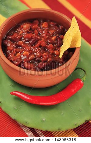 Mexican table setting with chilly with meat in a traditional bowl served on a cactus with nachos and hot pepper