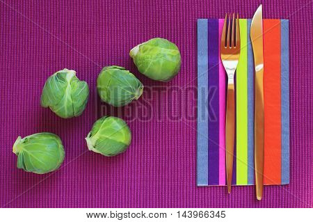 Fresh brussels sprouts ready to be served or prepared for a healthy eating lifestyle fork and knife placed on a colorful napkin.