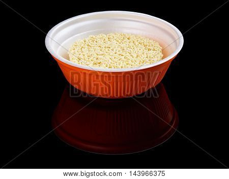 Instant noodles in red plastic plate isolated on black reflecting background