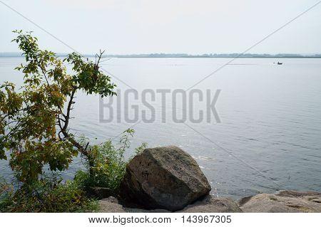 Riverside lone stone lonely tree blue water blue sky motorboat far.