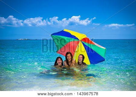 Three beautiful attractive young women with umbrella having fan on the beach