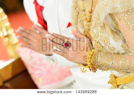 Thai wedding style ceremony with bride and groom hand