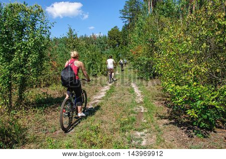 A group of tourists on a mountain bike ride on dirt roadagainst a beautiful sky.