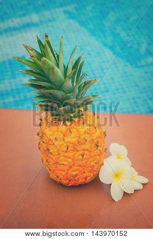 Raw whole yellow pineapple with flowers and tiled pool, retro toned
