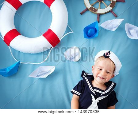 two years old boy playing in sailor hat. Child with a steering wheel and paper ships on blue background