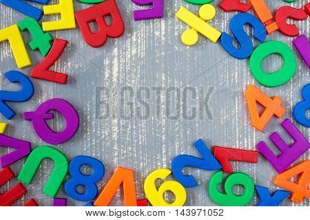 Border of colorful toy magnetic letters and numbers over a grey wooden background