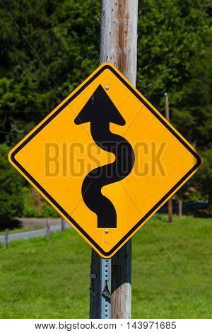 Kirkwood PA - August 23 2016: A yellow curvy road ahead symbol sign on a highway.