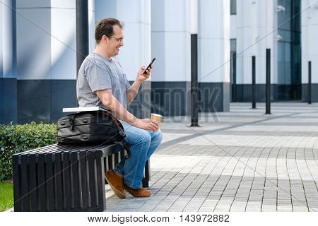Middle age man reading tablet sitting outdoors