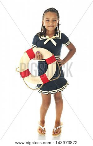 A young elementary girl happily holding a life ring while wearing her blue and gold sailor dress.  On a white background.