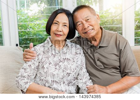 Happy senior Asian couple smiling and hugging at home