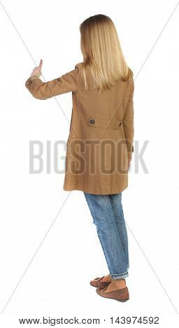 Back view of  pointing young women in parka. Young girl gesture. Rear view people collection.  backside view of person.  Isolated over white background. The blonde in a brown cloak finger presses the