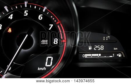 Glowing dial and needle showing zero engine speed in car interior