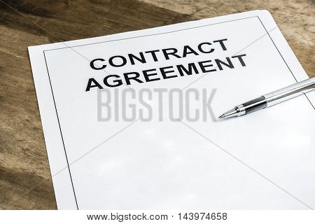 Pen on blank contract agreement paper template on wooden background