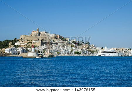 Ibiza Spain - June 3 2016: View of the Dalt Vila (Upper Town) of Eivissa (Ibiza Town) with its cathedral lighthouse an old sailboat and a modern yacht