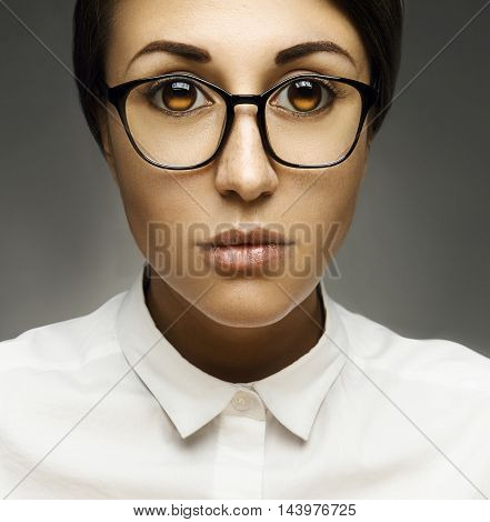 Beauty Model Girl In Sexy Glasses. Young Teacher Brunette Woman In Studio On Gray Background