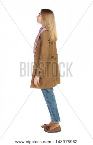 back view of standing young beautiful  woman.  girl  watching. Rear view people collection.  backside view of person. The blonde in a brown cloak, standing sideways and looking up.