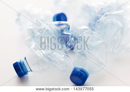 recycling, reuse, garbage disposal, environment and ecology concept - close up of empty used crashed plastic water bottles on table