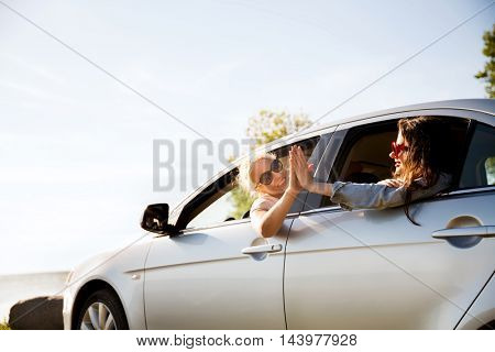 summer vacation, holidays, travel, road trip and people concept - happy teenage girls or young women in car at seaside making high five gesture