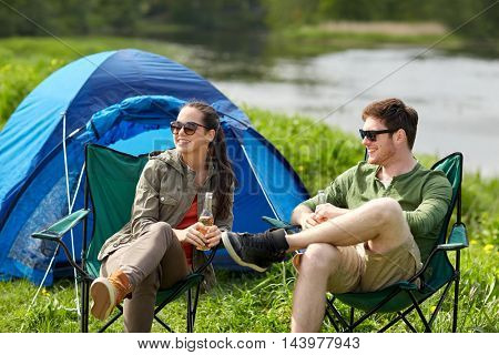 camping, travel, tourism, hike and people concept - happy couple drinking beer or cider at campsite