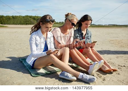 summer vacation, holidays, technology, travel and people concept - group of happy young women with smartphones on beach