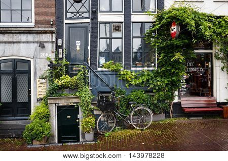 Amsterdam Netherlands - July 01 2016: Parked bicycle near a traditional Amsterdam house in rainy weather