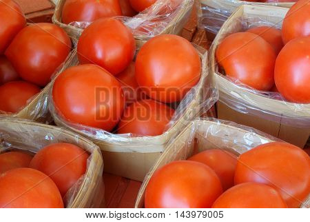 fresh red tomatoes baskets at the market
