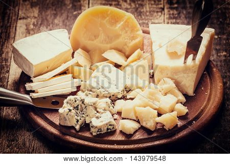 Composition Of Cheese, Berries, Bottles And Glasses Of Wine On A Wooden Table
