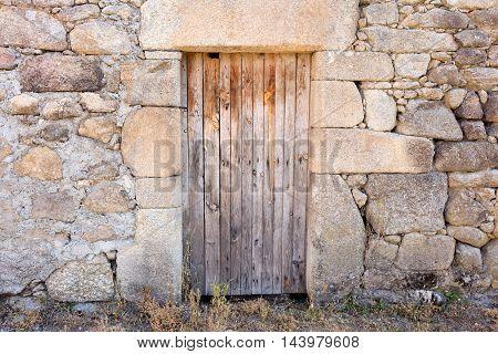 old wooden door the wall around is built with stones