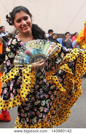 Cajamarca Peru - February 7 2016: Woman with multicolored flowered dress and fan marches in Carnival parade in Cajamarca Peru on February 7 2016