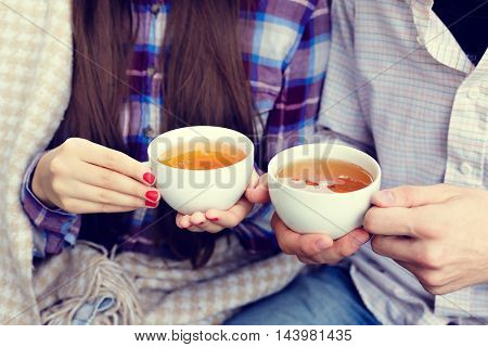 Young man and woman holding a cup of a tea