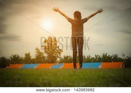 Woman pulls hands to the sky on green grass in stadium. Vintage tone.