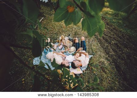 Happy family on the lawn in the park. Photo from tree