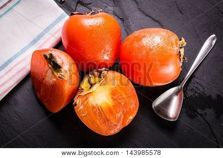 Delicious orange persimmons on wooden table , healthy food.