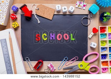 Small blackboard surrounded with various stationary with the word School in the middle on wood background