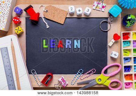 Small blackboard surrounded with various stationary with the word Learn in the middle on wood background