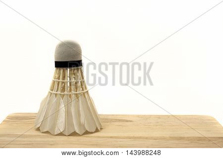 Badminton shuttlecock on wooden and white background