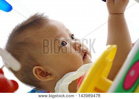 Cute Asian infant baby playing in baby walker