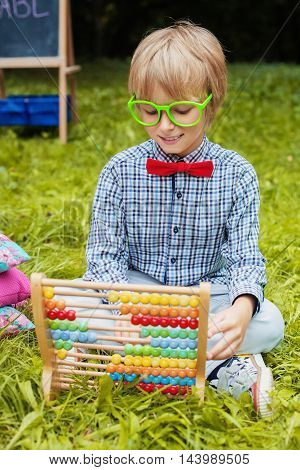cheerful little boy counting on abacus. The concept of training and education.