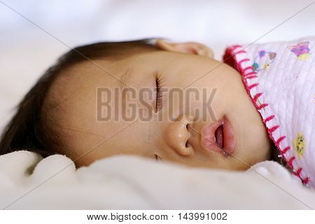 Cute Asian infant baby is sleeping under blanket on her bed.
