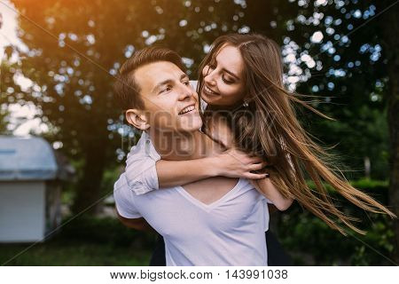 Young man carries his girlfriend on his back in the park