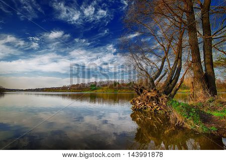 Lake shore and a beautiful cloudscape. Sky and clouds reflection on Lake