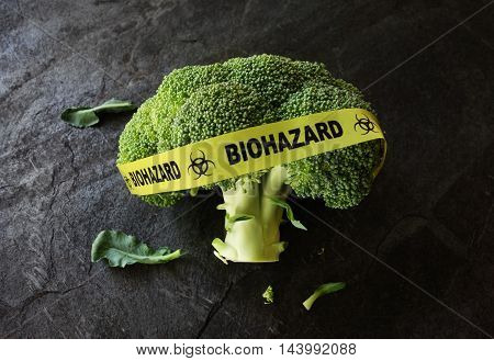 Yellow Biohazard tape on a piece of broccoli -- food safety concept