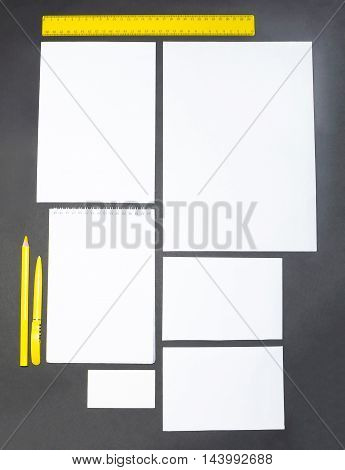 Mock-up business template with cards, papers, pen on gray background.