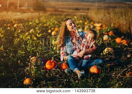 mother and daughter on a field with pumpkins, Halloween eve