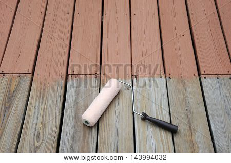 close up on roller and painted wooden deck