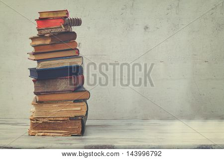 stack of books on white wooden background, retro toned